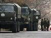 Neoznačená vojenská vozidla a ozbrojení muži na kontrolním stanovišti...