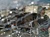 Pohled na místo útoku skrze výbuchem roztříštěné čelní sklo auta.