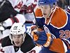 Hon na puk. Eric Gelinas (22) z New Jersey Devils a Leon Draisaitl (29) z...