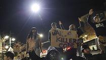 """Demonstranti s plakátem (volně přeloženo) """"vězení pro policistu - vraha"""""""