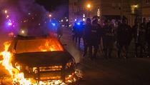 Policist� pochoduj� vst��c demonstrant�m pod�l ho��c�ho auta.