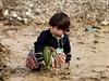 Syrské uprchlické děvčátko sedí v blátě u libanonského města Al-Faour.