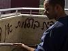 Smývání protiarabského graffiti nápisu.