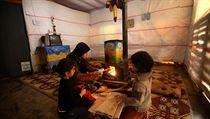 Syrští uprchlíci v improvizovaném stanu v Libanonu. Kamna, sušák a televize pro nejnovější informace o dění v Sýrii.