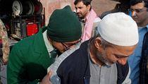 Student pl��e na rameni mu�e pot�, co byl zachr�n�n ze �koly, kde Taliban povra�dil p�es 100 lid�.
